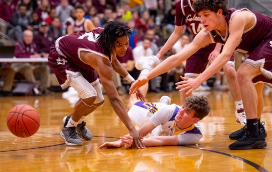 Lyon County's Gabe Board (22) gets a pass away between Henderson County defenders Zac Green (2) and Cory Stewart (1) during the Boys Second Region Tournament at Madisonville-North Hopkins High School Tuesday night.
