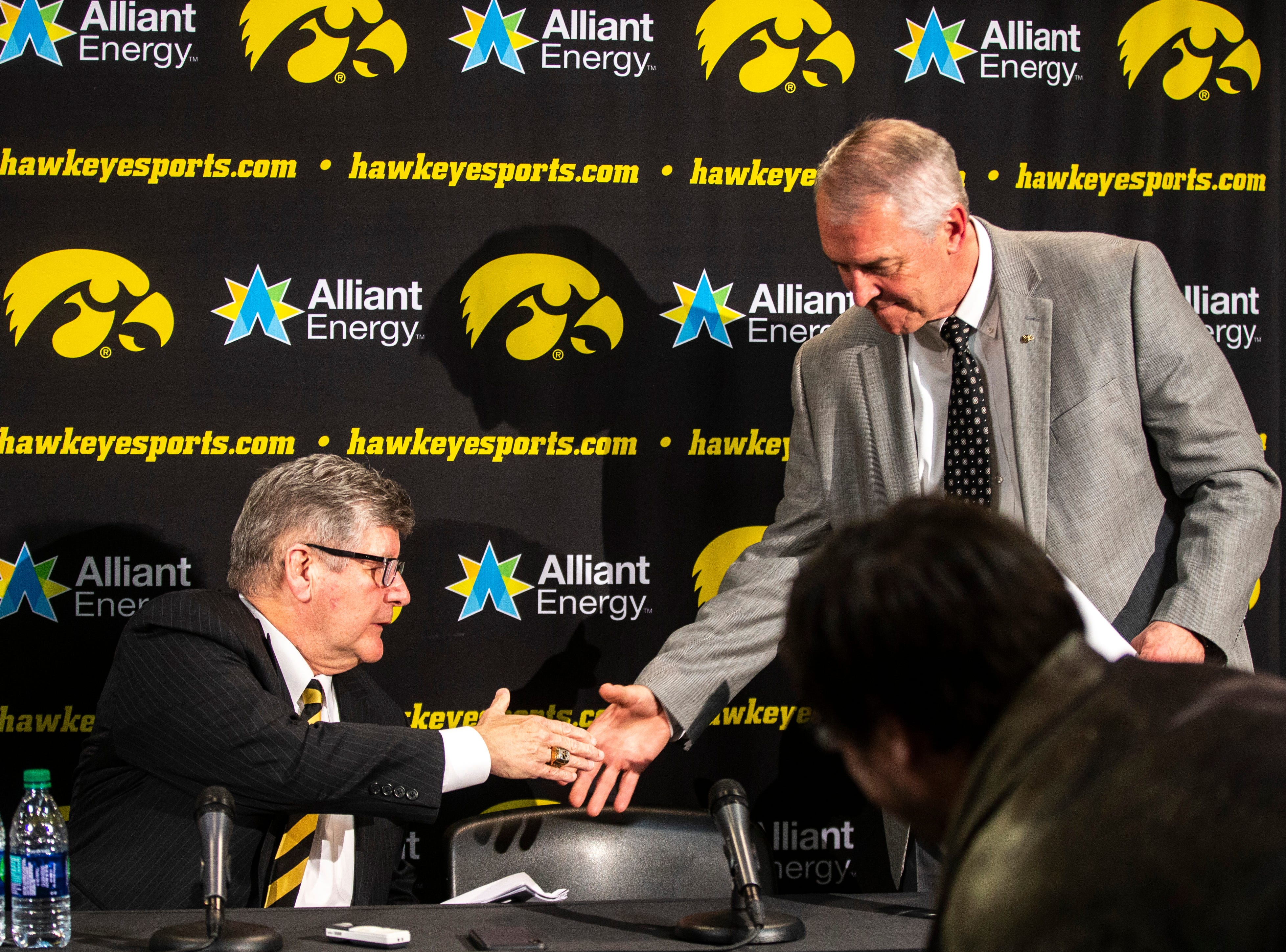 Iowa play-by-play commentator Gary Dolphin, left, and Iowa athletic director Gary Barta shake hands during a press conference on Wednesday, Feb. 27, 2019, at Carver-Hawkeye Arena in Iowa City, Iowa.