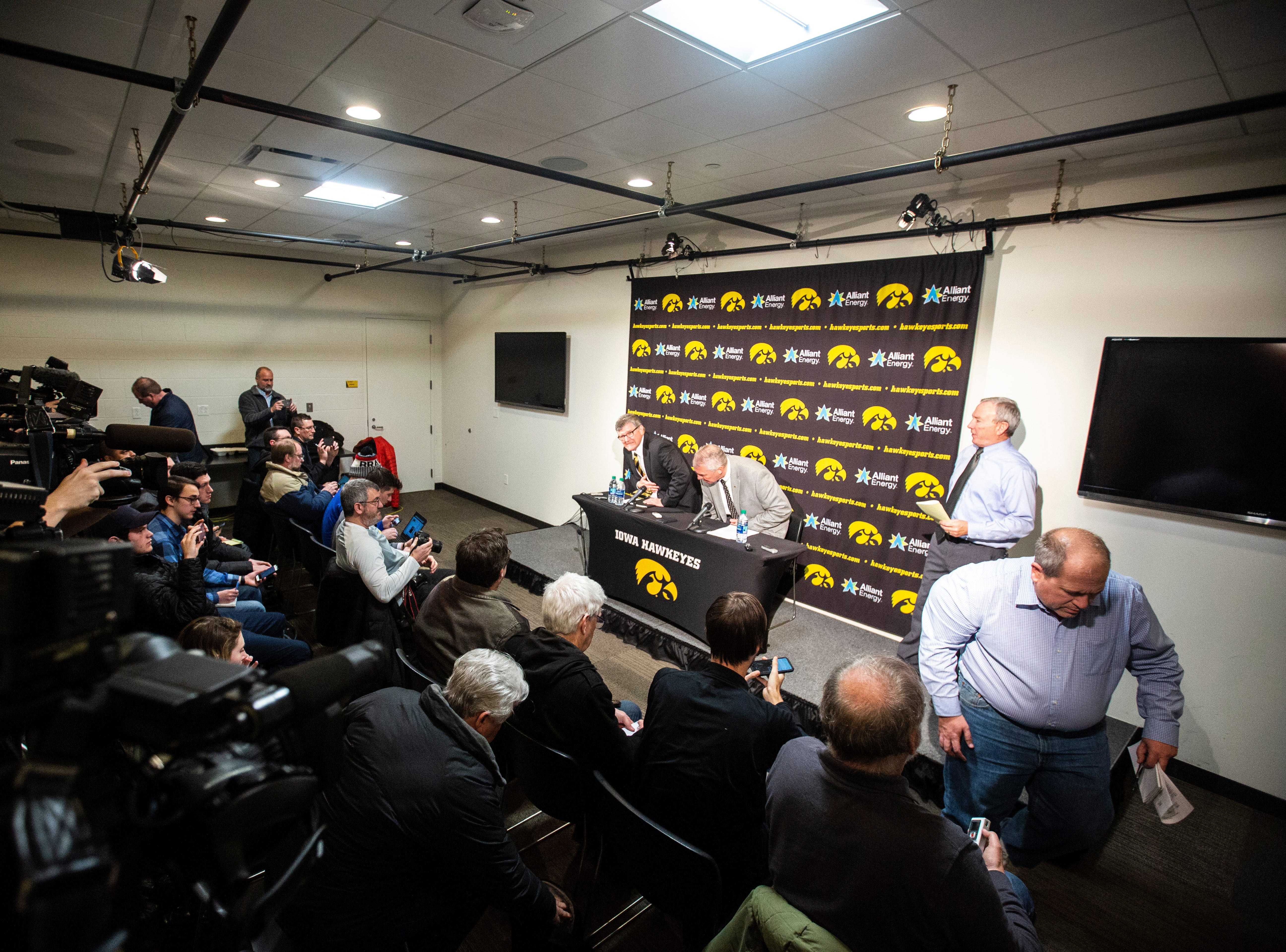 Iowa play-by-play commentator Gary Dolphin, left, and Iowa athletic director Gary Barta walk into a press conference on Wednesday, Feb. 27, 2019, at Carver-Hawkeye Arena in Iowa City, Iowa.