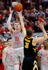 Ohio State forward Justin Ahrens, left, goes up for a shot against Iowa guard Jordan Bohannon during the second half of an NCAA college basketball game in Columbus, Ohio, Tuesday, Feb. 26, 2019. Ohio State won 90-70.