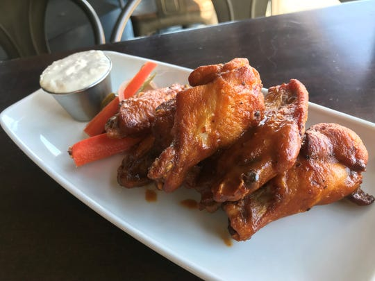 Smoked wings coated in barbecue sauce and served with pickled vegetables and horseradish parmesan dressing at Upland Brewing Co. on College Avenue in Indianapolis.