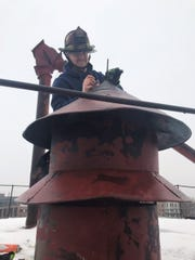 Fishers Fire Capt. Todd Rielage prepares to bring down an old emergency siren from the top of a grain elevator downtown