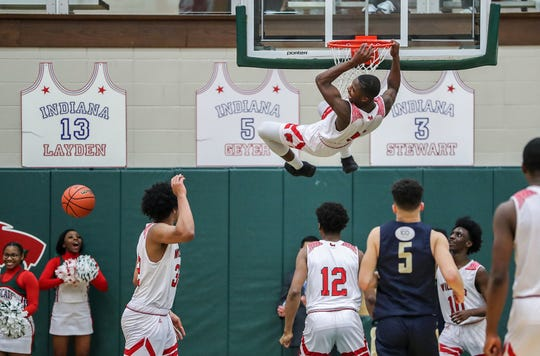 Lawrence North Wildcats guard Jared Hankins (5) pulls himself up to the basket after a dramatic dunk late in the second half of sectional quarterfinals, as the Wildcats clinch their win over Cathedral, at Lawrence North High School in Indianapolis on Tuesday, Feb. 26, 2019. Lawrence North won, 65-59.