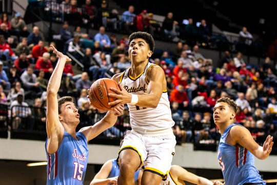 Bettendorf point guard DJ Carton (11) drives to the basket while Dubuque Senior's Landon Hermsen (15) and Dubuque Senior's Noah Carter, right, defend during a Class 4A substate boys' basketball game on Tuesday, Feb. 26, 2019, at the U.S. Cellular Center in Cedar Rapids, Iowa.