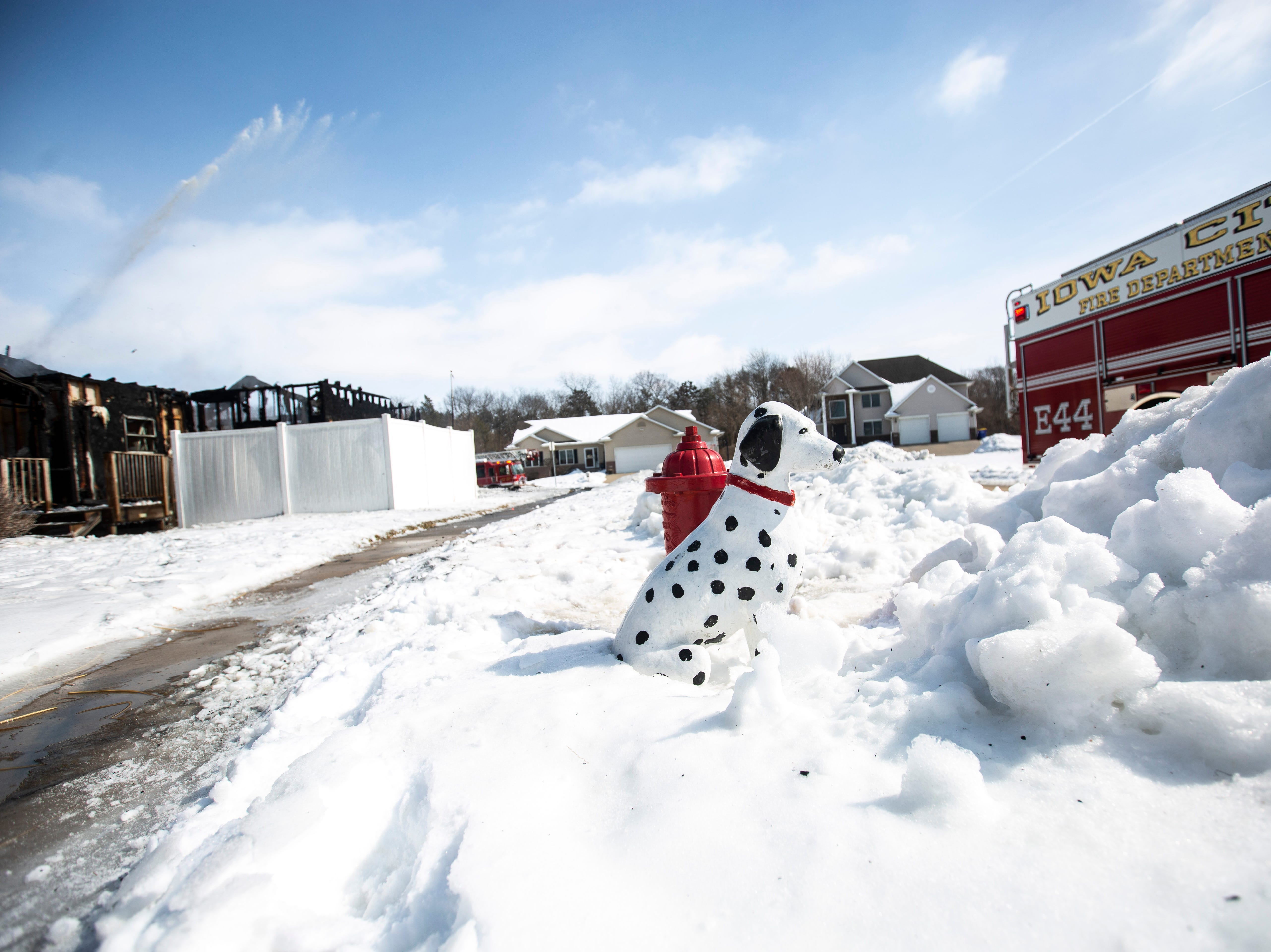 A Dalmatian statue sits next to a fire hydrant while fire crews work to settle a blaze that fully engulfed the garage and spread into the roof of a residential home on Wednesday, Feb. 27, 2019, at 404 Serenity Court in Solon, Iowa.