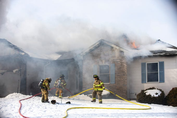 Fire crews work to settle a blaze that fully engulfed the garage and spread into the roof of a residential home on Wednesday, Feb. 27, 2019, at 404 Serenity Court in Solon, Iowa.
