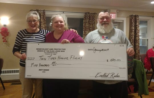 Rita Carlson, left, Elks Exalted Ruler, presents a $500 check to Tammy and Chip Longabaugh, from Twin Tiers Honor Flight.