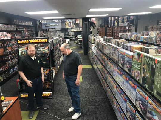 Sci-Fi City store manager Walt Ricketts (left) and owner Frank Uchmanowicz survey water damage Feb. 26, 2019. After 10 days of rain, 3,000 gallons of water seeped up through the store's concrete floor, standing two inches deep on the carpet.