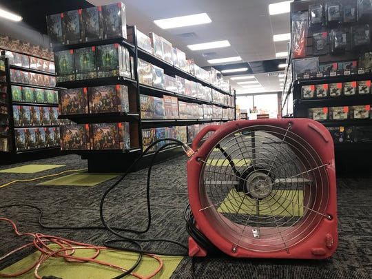 One of several fans dries out the carpet Feb. 26, 2019, at Sci-Fi City on North Broadway, after heavy rain left 3,000 gallons of water seeping up through the floor.