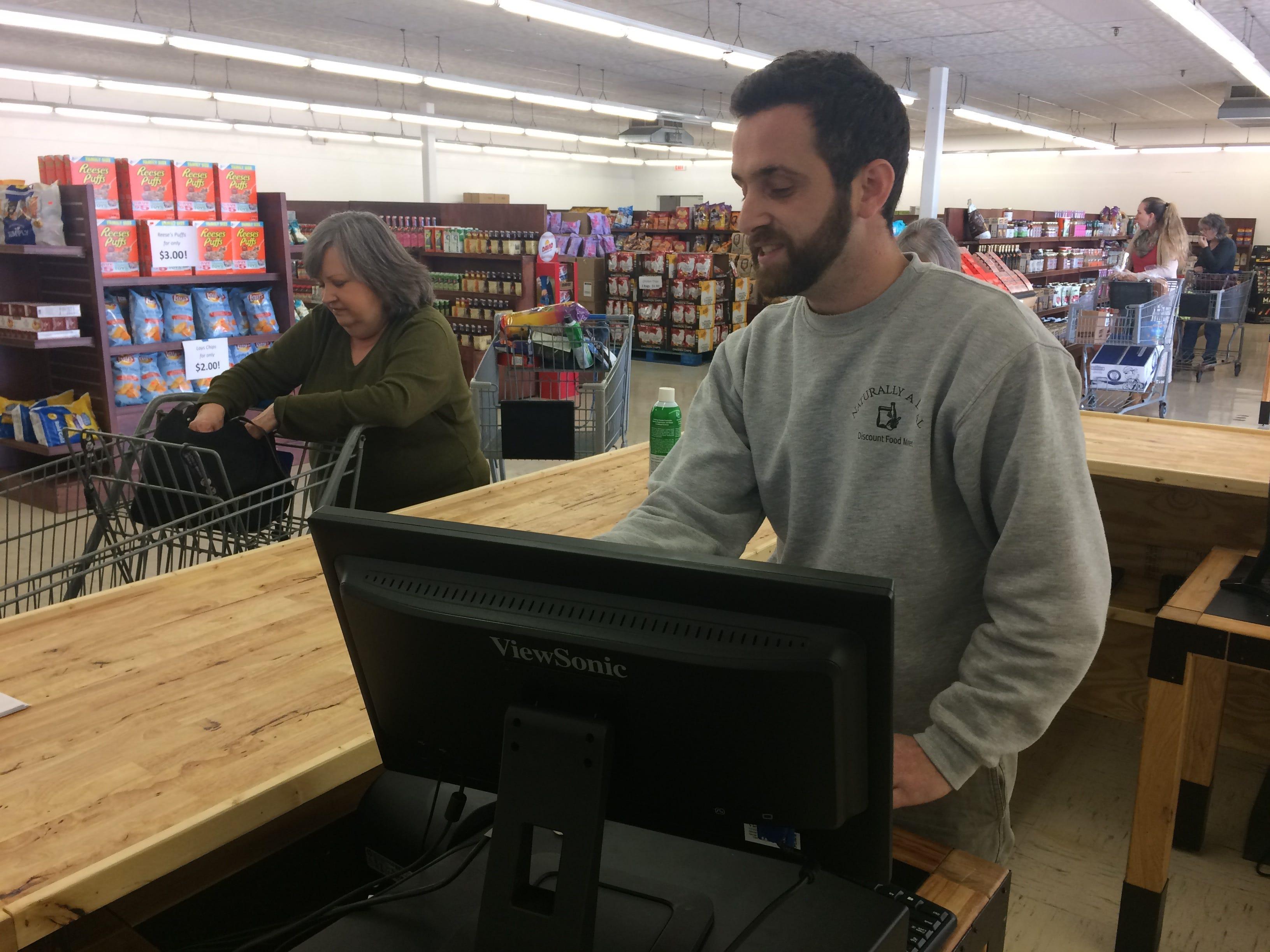 Jon Einwechter, owner of Naturally a Deal, handles the register while Kathy Schaffer of Powell checks out.