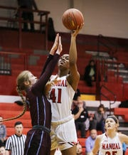 Manual's Nila Blackford (41) puts up a layup over Assumption's Abby McQueary (4) during their game at Manual High School. Feb. 26, 2019