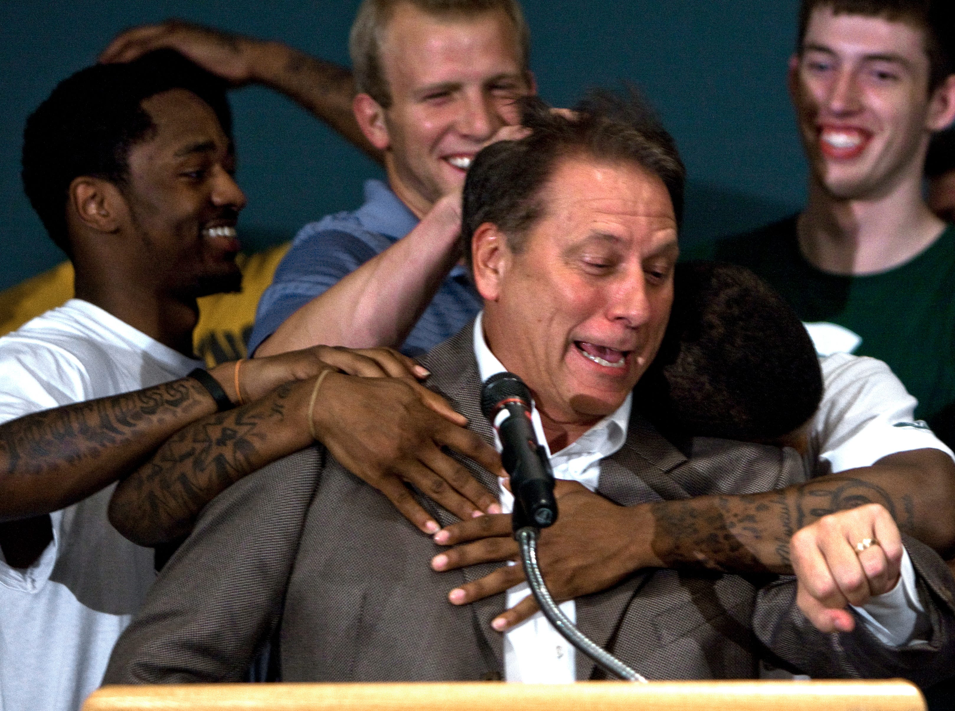 Tom Izzo is hugged by Korie Lucious, and flanked by (l. to r.) Kalin Lucas, Austin Thornton, and Garrick Sherman near the end of the press conference Tuesday evening, June 15th, 2010 where it was announced that Izzo would remain at the helm of the MSU men's basketball team.