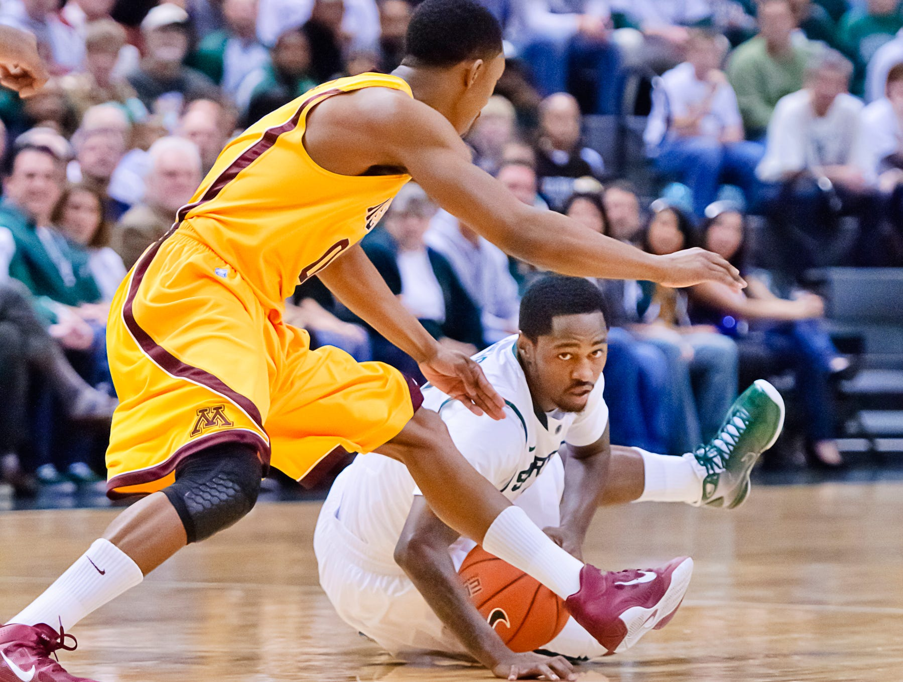 Kalin Lucas (right) of MSU slips as he attempts to drive aroun d Al Nolen of Minnesota during their game Friday December 31, 2010 in East Lansing.  Lucas was able to maintain possession of the ball.