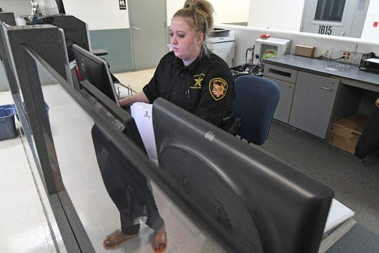 Corrections Officer Alexandria Reinhardt books an inmate into custody in this News Journal file photo in the Richland County Jail.