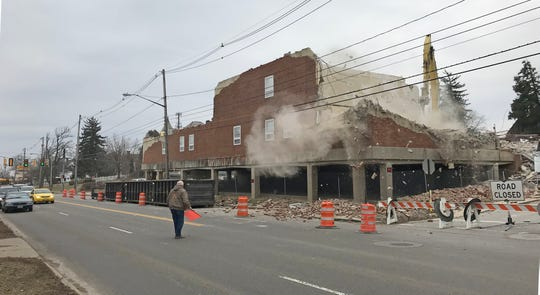 Traffic was delayed Wednesday afternoon as the north facade of the former YMCA building on Park Avenue West was demolished.