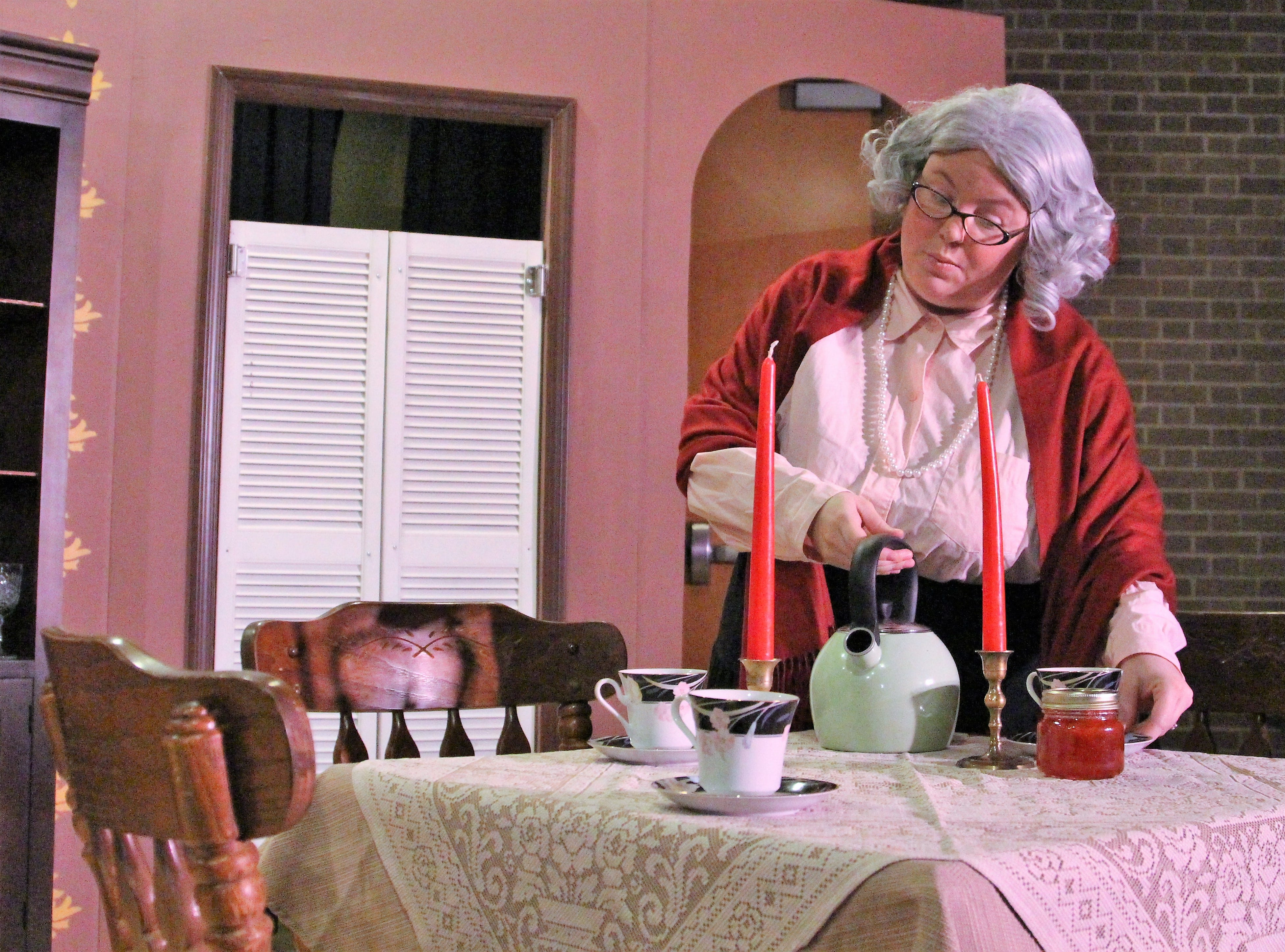 Spinster Martha Brewster, played by Amanda Ash, pours herself a cup of tea during a lively family conversation with her nephew Mortimer, a drama critic for  a New York newspaper. The student-led production at the Ohio State University at Marion follows the insane Brewster family who descended from the Mayflower settlers.