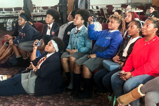 Members of Freedom Prep's girls rugby team watch themselves in a  documentary made by Nike on Wednesday.