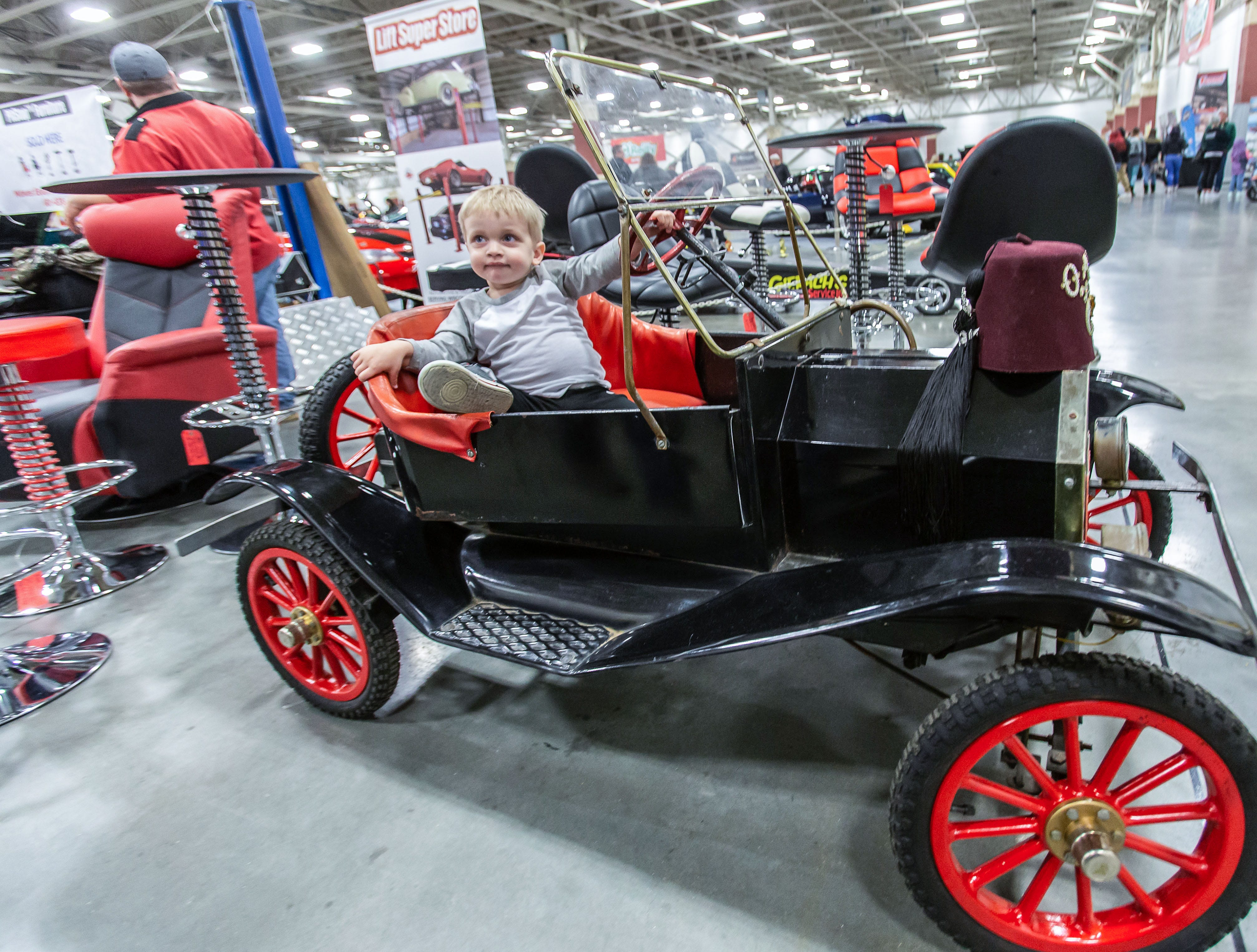 Two-year-old Cole Lampman of Oak Creek finds a suitable ride during the 57th annual O'Reilly Auto Parts World of Wheels at State Fair Park in West Allis on Saturday, Feb. 23, 2019. The event features over 300 vehicles, celebrity appearances, vendors, a charity auction and more.