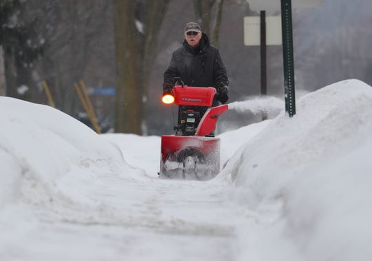 A man clears snow on a sidewalk along  West Bender Road in Milwaukee on Wednesday. The latest snowfall dropped an inch or 2 overnight on the area.