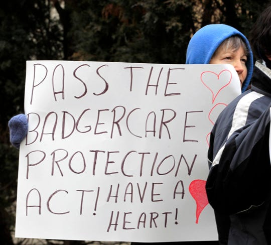 A protester rallies outside a Milwaukee hospital in 2013 after then-Gov. Scott Walker's decision to turn down federal funding to expand BadgerCare.