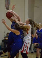 Norfork's Kynzie Rangel battles St. Paul's Kaya Harp and Jackie Phillips for a rebound on Tuesday night in the first round of the Class 1A State Tournament.