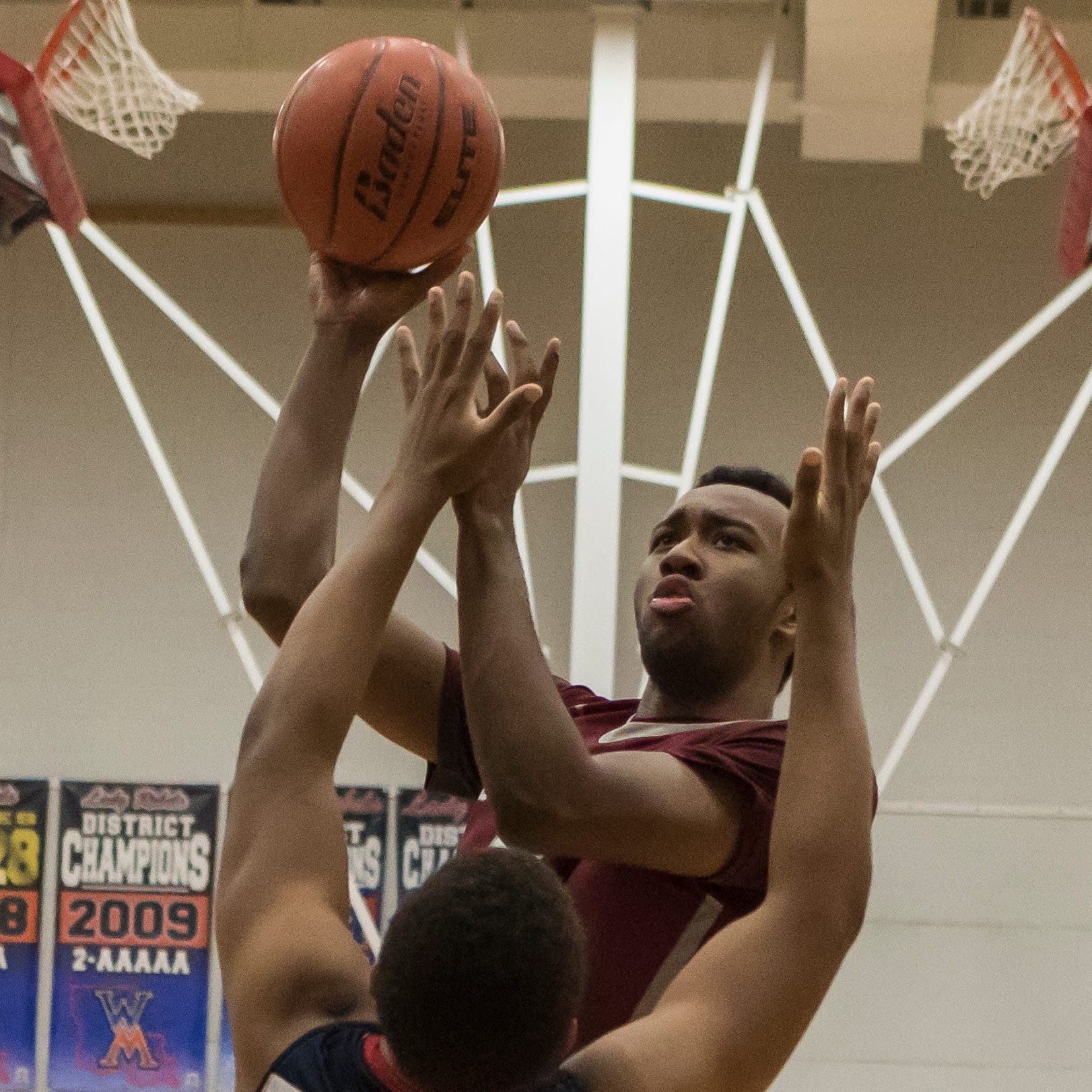 Ouachita's Myron Washington (5) shoots a basket while West Monroe's Dontrell Cobbs (12) attempts to make the block during the second round of class 5A playoff basketball at West Monroe High School in West Monroe, La. Ouachita would win the game 58-46.