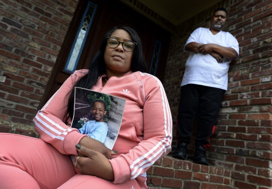 "Trixie Williams holds a picture of her son Kevin Buford as her husband, Douglas, stands behind her Feb. 14, 2019, at their Nashville home. Buford was sentenced at 16 to life in prison for murder. She thinks her son deserves a second chance. ""He shouldn't be just thrown away,"" she said."