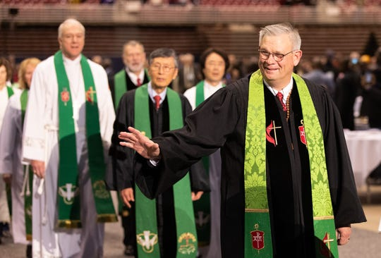 Bishop William McAlilly (right) greets delegates as the bishops process into opening worship for the 2019 United Methodist General Conference in St. Louis.