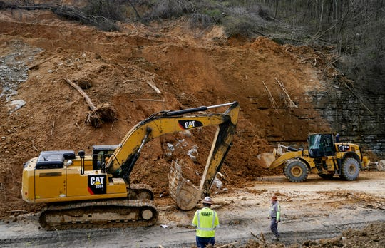 Tennessee Department of Transportation workers clean up debris from a landslide that occurred Saturday night along I-24 eastbound near mile marker 42 in the Whites Creek area  Wednesday, Feb. 27, 2019 in Nashville, Tenn.