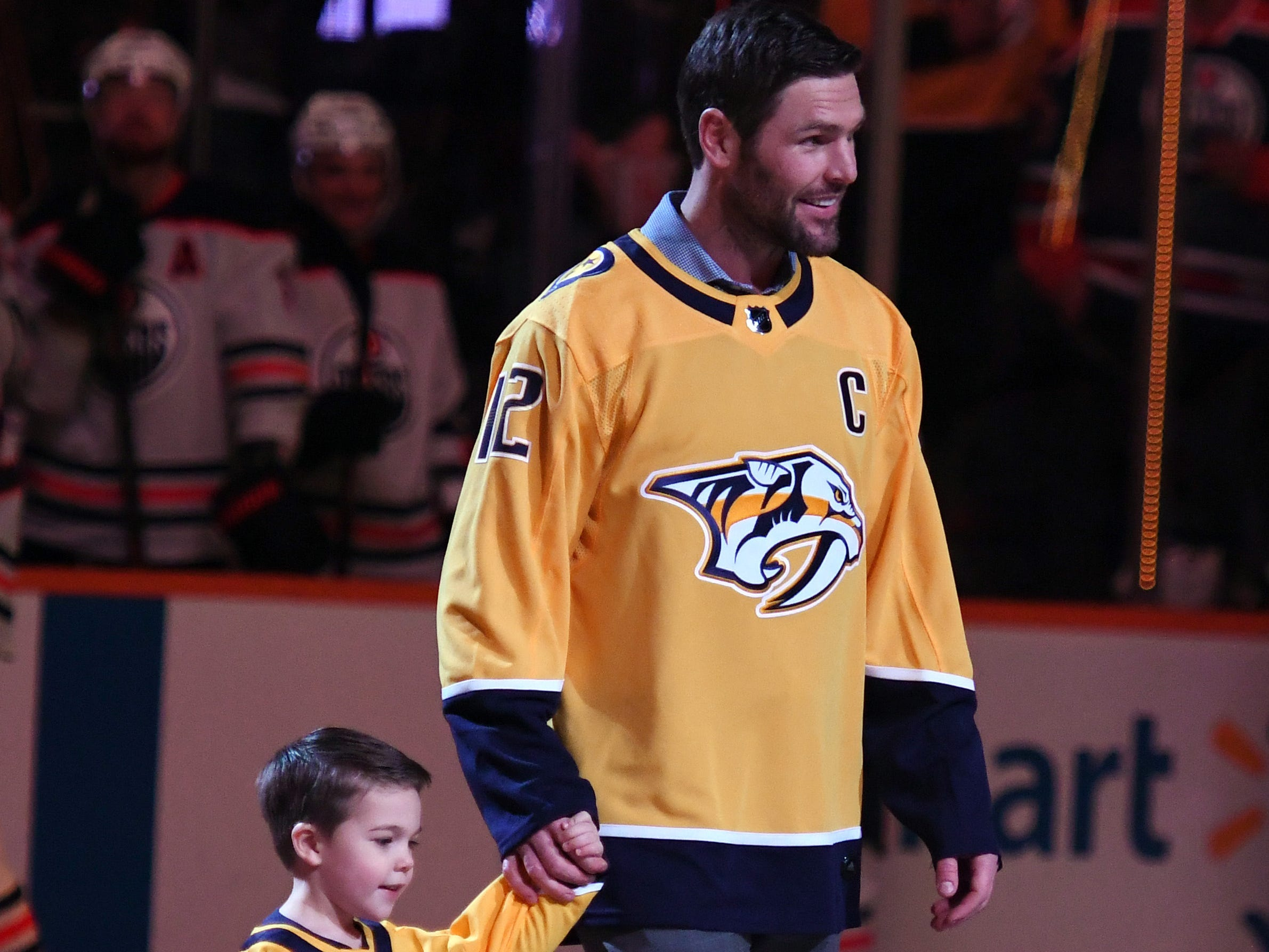 Former Nashville Predators captain Mike FIsher (right) is joined by his son Isaiah Fisher (left) as he is honored prior to the game against the Edmonton Oilers at Bridgestone Arena.