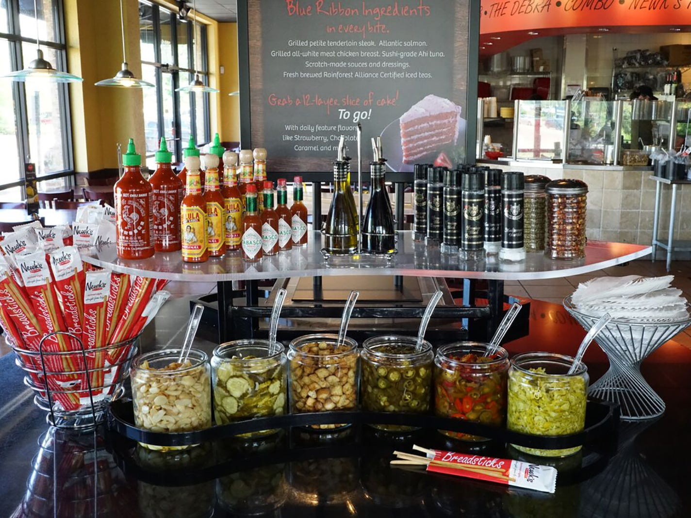 The Gourmet Roundtable at Newk's Eatery features complimentary bread and butter pickles, house-made croutons, sliced cherry peppers, capers, shredded Parmesan, freshly roasted garlic and imported breadsticks, jalapenos and pepperoncini peppers.