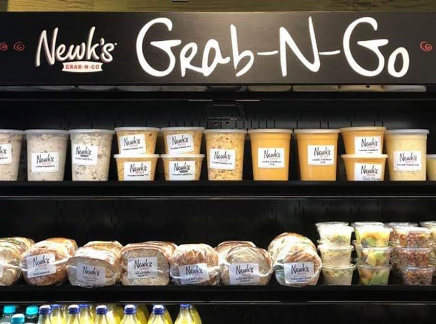 Newk's Eatery has a Grab-N-Go cooler where patrons can pop in to quickly pick up many of the chains signature salads, sandwiches, soups and slices of cake made fresh daily without the wait.
