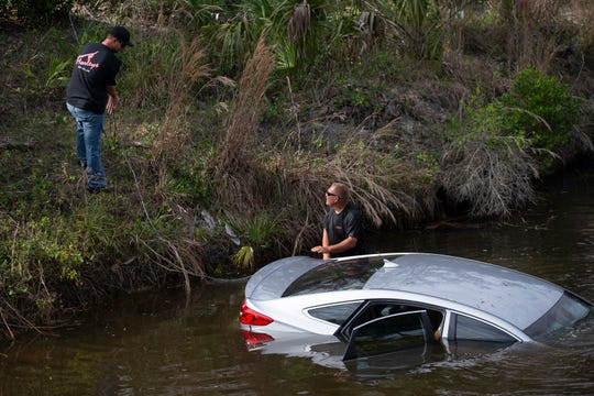 Tow truck operators prepare to remove a vehicle from a canal Wednesday, Feb. 27, 2019, at the intersection of Tarpon Bay Boulevard and Spanish Oaks Lane in North Naples.