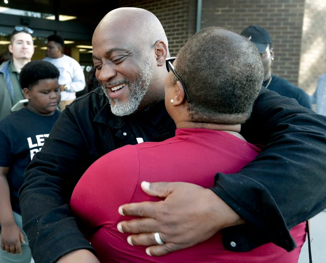 Former felon Desmond Meade, president of the Florida Rights Restoration Coalition, left, hugs Melanie Campbell with the National Coalition Black Civic Participation after registering to vote at the Supervisor of Elections office Tuesday, Jan. 8, 2019, in Orlando, Fla.