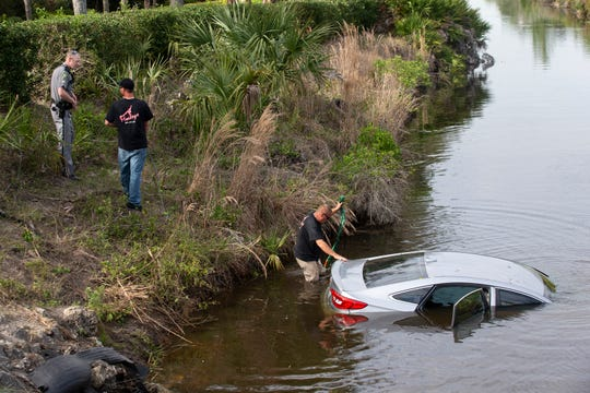 Crews attempt to recover a vehicle in a canal Wednesday, Feb. 27, 2019, at the intersection of Tarpon Bay Boulevard and Spanish Oaks Lane in North Naples.