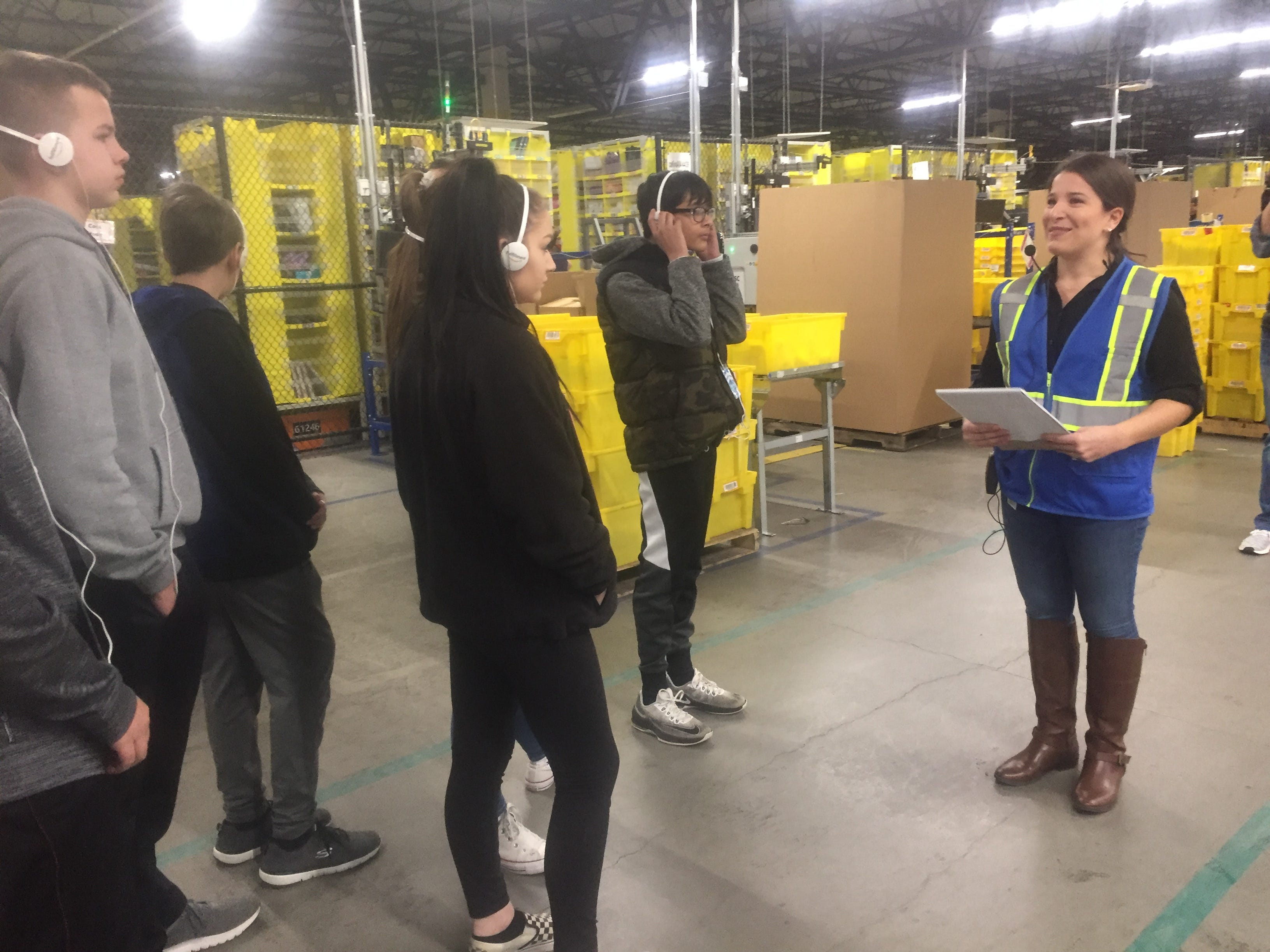Amazon spokesperson Ali Hutchins (right) leads Southwest Licking students, step-by-step, through the Amazon fulfillment process during a Feb. 26 Etna facility tour.