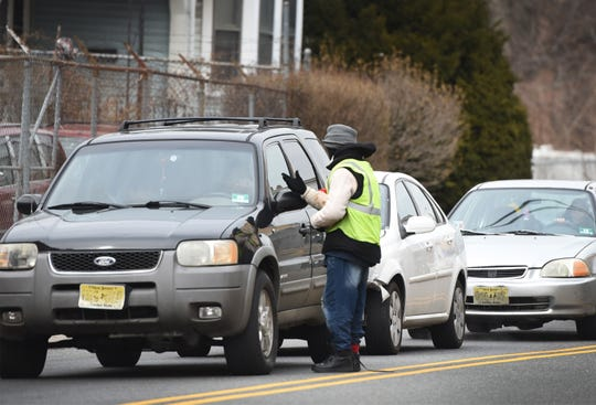 Photo of a man asking drivers whether or not they need their windshield cleaned while cars stop at the light at the corner of Broadway and Straight Street, just across the street from White Castle in Paterson, photographed on 02/27/19.
