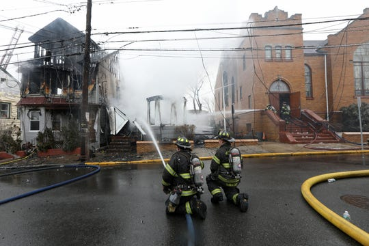 Firefighters continue to spray water on a Hopper Ave. fire in Paterson.  The fire destroyed  two homes and went to at least four alarms. Wednesday, February 27, 2019