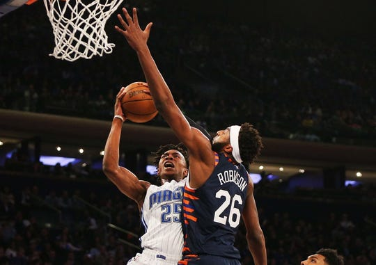 Orlando Magic forward Wesley Iwundu (25) goes up for a shot while being defended by New York Knicks center Mitchell Robinson (26) during the first half at Madison Square Garden.