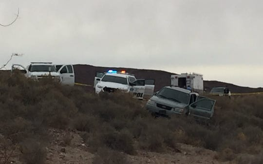 New Mexico State Police and other agencies investigate following an officer-involved shooting along Interstate 25 north of Las Cruces. The suspect was shot while allegedly barricaded inside the green Ford Escape at the forefront of the photo.