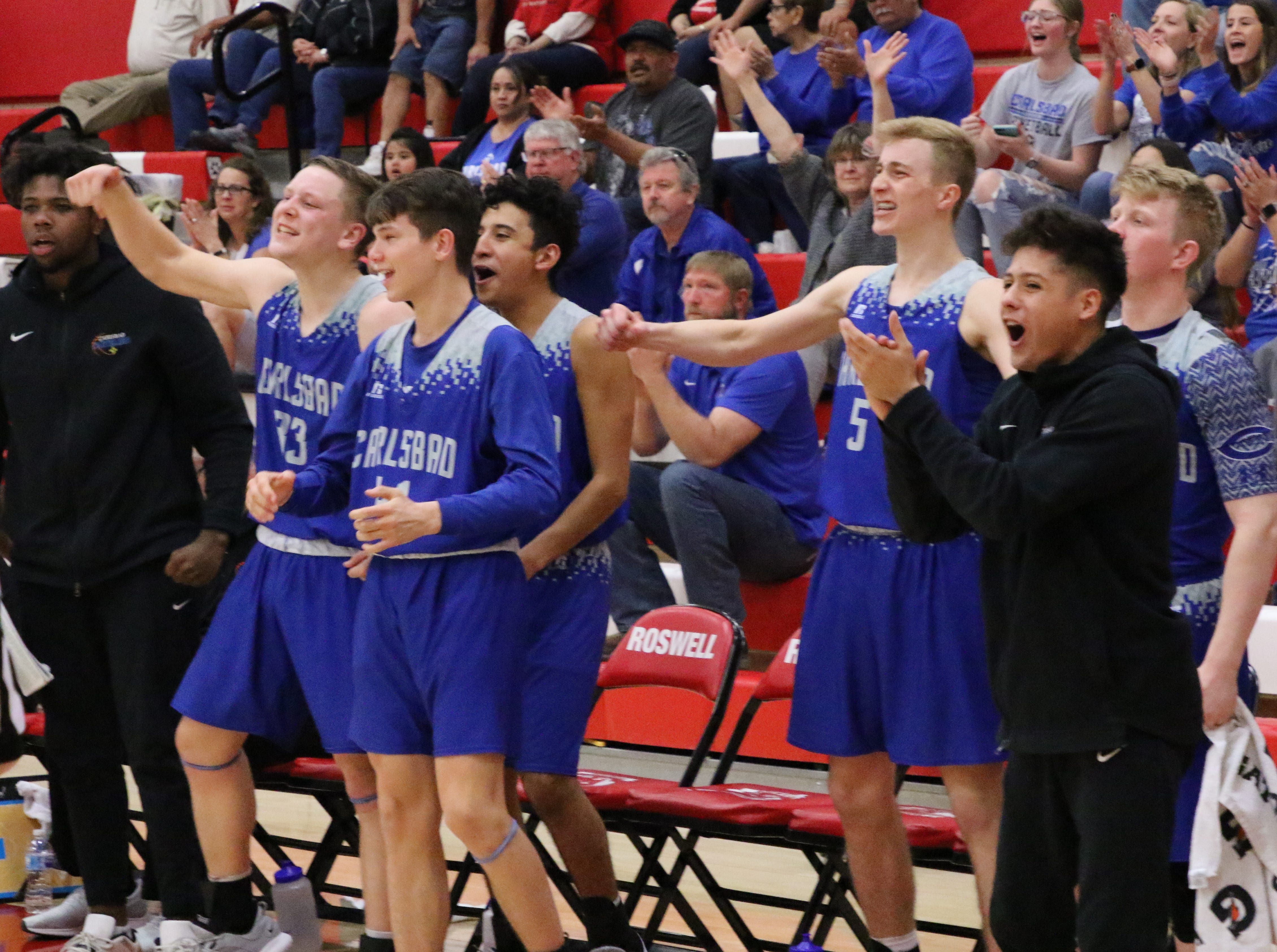 Carlsbad's bench erupts after Matt Fernandez made his first 3-point shot in the fourth quarter of Tuesday's Class 4-5A tournament game against Roswell. Carlsbad went on a 16-2 run to start out the final quarter.