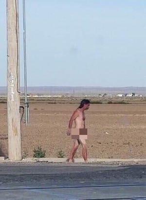 An unidentified man walks along the side of U.S. highway 285 and Grandi Road Feb. 25.