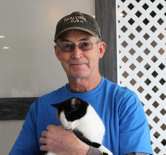 Ed Denton of Kitty City NM holds one of Kitty City's adoptable cats.