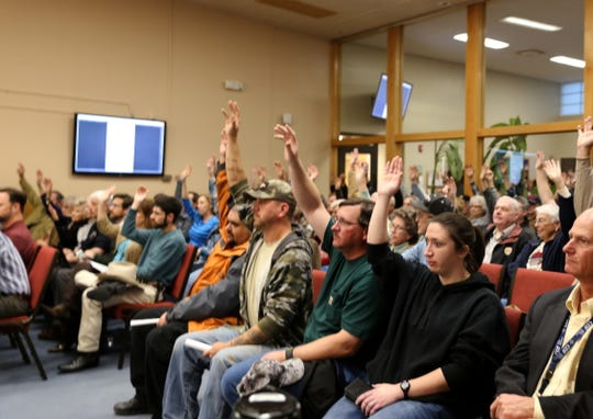 Audience members raise their hands, Tuesday, Feb. 26, 2019, to show support for a Second Amendment Preservation City resolution during the Farmington City Council meeting.