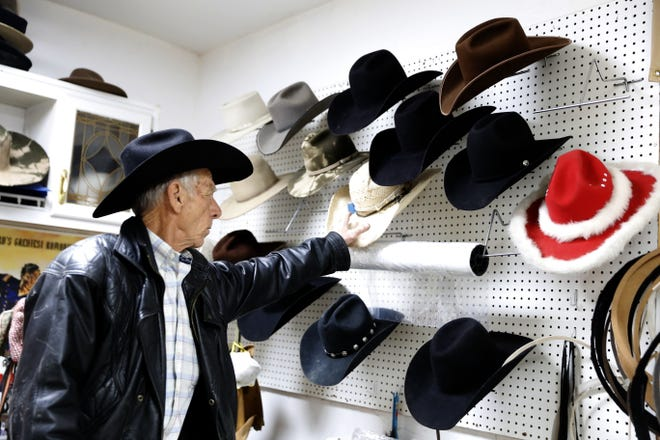 Ramie Harper points to a hat on the wall of his hat shop, Tuesday, Feb. 26, 2019, in Fruitland.