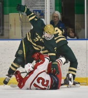 Canton's James Monteith is plowed over by Howell Highlander Dominic Rossi on Feb. 26 at the Farmington Ice arena.