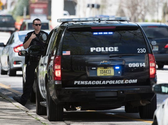 A Pensacola Police Officer monitor the situation during a routine traffic stop in downtown Pensacola on Wednesday. The city of Pensacola is considering an ordinance to allow retired officer to return to work on a part-time basis.
