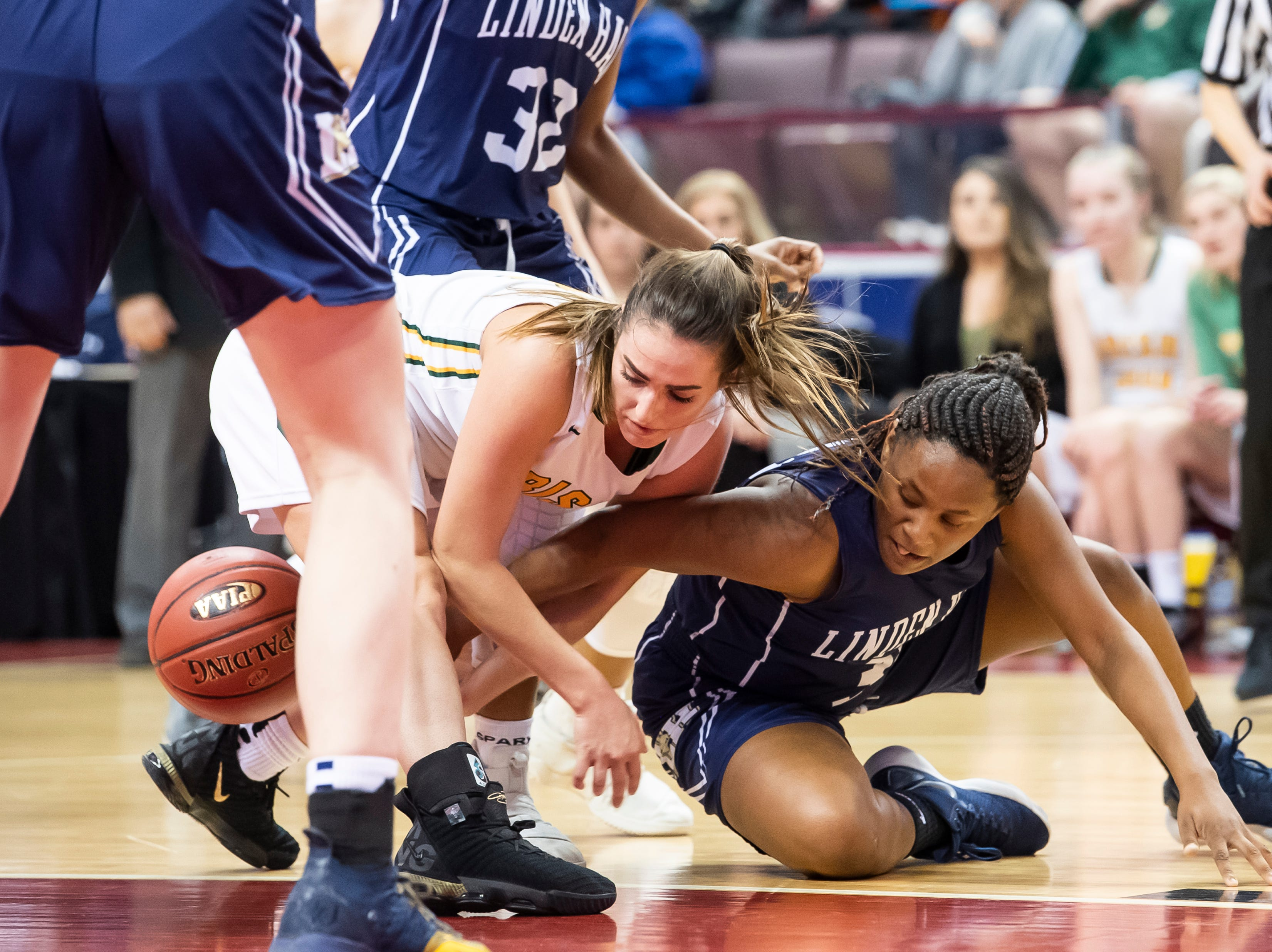York Catholic's Gina Citrone and Linden Hall's Tahri Phillips fight for possession during the District 3 2-A girls championship game against Linden Hall at the Giant Center in Hershey Tuesday, Feb. 26, 2019. The Fighting Irish fell 56-27.