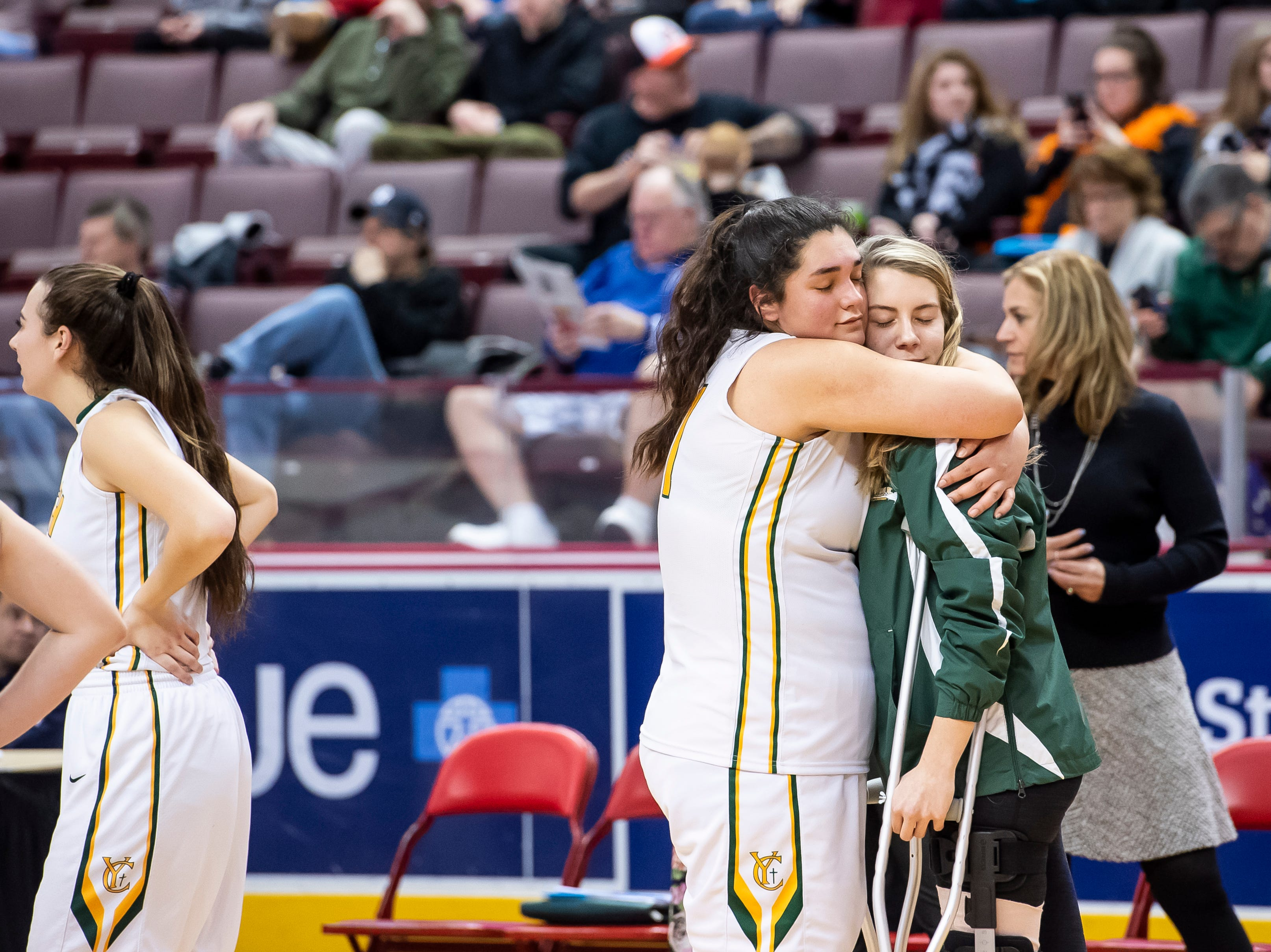 York Catholic's Gabby Coley, left, hugs her teammate Sarah Reed after the Fighting Irish fell in the District 3 2-A girls championship game against Linden Hall at the Giant Center in Hershey Tuesday, Feb. 26, 2019.