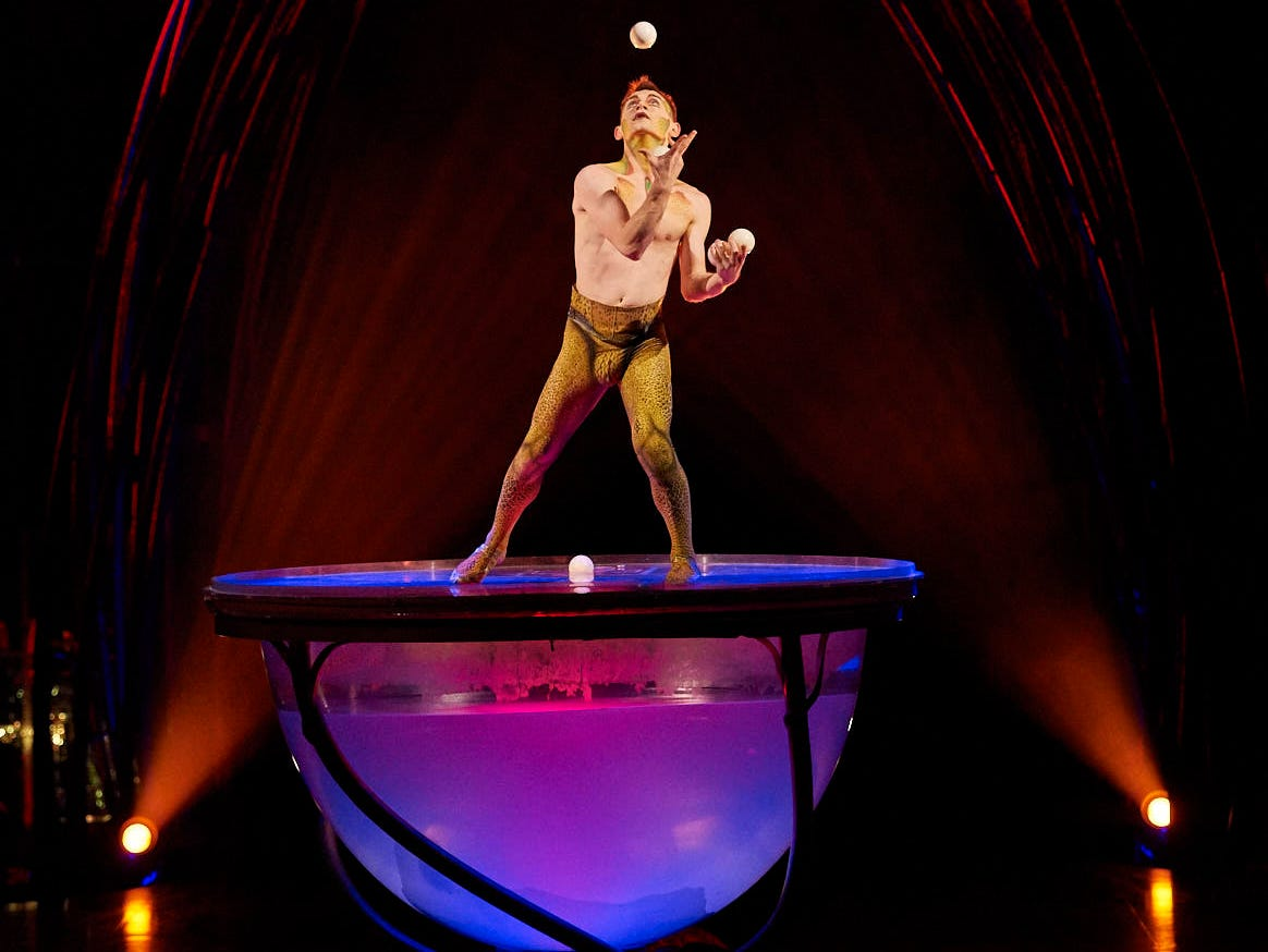 A cast member performs a juggling act with balls that drop in ever greater numbers from the sky above in Cirque du Soleil.